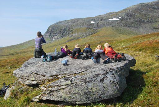 Ungdommer ser i kikkert etter en reinsflokk. De ligger alle på en stor stein. Foto: Fjelldriv
